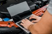 Partial View Of Auto Mechanic Working On Laptop With Blank Screen At Automobile With Opened Car Cowl poster