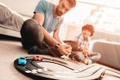 Bearded Father And Son Playing With Toy Race Road. Man Sitting On Floor. White Carpet In Room. Toy C poster