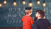 Teacher With Beard, Father Teaches Little Son In Classroom, Chalkboard On Background. Favourite Teac poster