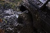 Fragment Of Car Stuck In Dirt, Close Up. Wheel In Deep Puddle Of Mud Overcomes Obstacles. Offroad Ti poster