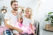 Cute Little Child In Pink Tutu Skirt Applying Makeup To Happy Father poster