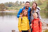 Young family standing on the shore of a lake in the countryside looking to camera smiling, Lake Dist poster