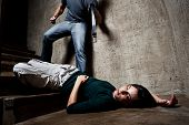 pic of domestic violence  - Battered woman lies lifelessly at the bottom of stairs with a faceless man holding a belt - JPG