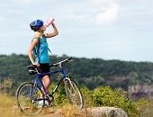 Attractive, healthy woman drinks from her water bottle on mountain bike. active outdoor lifestyle co