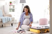 Pregnant Woman Writing Packing List For Maternity Hospital At Home poster