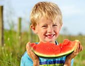 stock photo of toothless smile  - Young blond boy has healthy eating habits - JPG