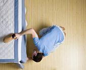 picture of peer-pressure  - Curious man peering underneath bed in search of his slipper - JPG