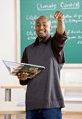 Teacher holding text book pointing to student in school classroom