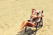 picture of bimbo  - Young beautiful blond woman on sunbed on the beach - JPG