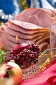 picture of christmas meal  - Holiday table setting with delicious whole baked sliced ham marinated peppers cherry tomatoes vegetable salad and glasses of red wine. Christmas decoration candles ornaments around.