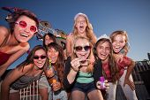 stock photo of bff  - Laughing teenage girls blowing bubbles at an amusement park - JPG