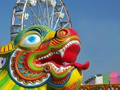 picture of dragon head  - Dragon head with tongue in front of a ferris wheel at a carnival - JPG