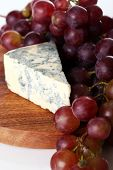 Slice of blue cheese and grape on the wooden surface