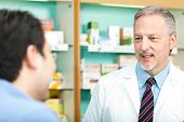 stock photo of erectile dysfunction  - Senior pharmacist dealing with a customer - JPG