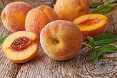 stock photo of peach  - fresh peaches with leaves on wooden background - JPG