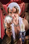 image of seer  - Grinning female fortune teller holding a crystal ball - JPG