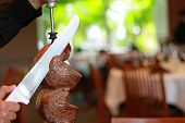 image of gaucho  - Brazilian steakhouse photo of a gaucho cutting a steak - JPG
