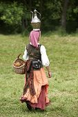 stock photo of gypsy  - Medieval gypsy woman carrying a pot on her head - JPG