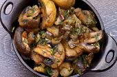 picture of stew pot  - Delicious Champignon Mushrooms Stew with Onion and Greens in Black Cast - JPG