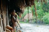 Papuan Boy From Dani Tribe Hides From A Rain Under A Roof.