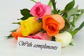 With compliments note and bouquet of colorful roses