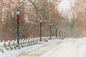 stock photo of lamp post  - A snow covered street lined with old style lamp posts and a white wooden fence that have been decorated with evergreen garland and red ribbons and bows - JPG