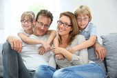 stock photo of cuddle  - Portrait of happy family of four wearing eyeglasses - JPG