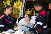 stock photo of ambulance  - paramedic team talking to young patient before she going into an ambulance - JPG