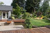 stock photo of lawn chair  - Back yard of a modern Pacific Northwest home featuring a deck spanning a creek - JPG