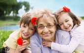 image of grandmother  - Closeup summer portrait of happy grandmother with grandchildren outdoors - JPG