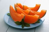 foto of cantaloupe  - Cantaloupe melon with mint as healthy refreshment close up