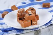 stock photo of toffee  - Many toffee on plate on napkin on wooden table - JPG