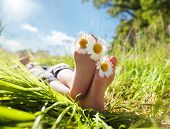 foto of toe  - Child with daisy between toes lying in meadow relaxing in summer sunshine - JPG