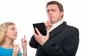 stock photo of shhh  - Father reading a tablet device shows shhh to his daughter - JPG