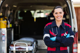 stock photo of ambulance  - attractive young female emergency medical service worker in front of ambulance - JPG