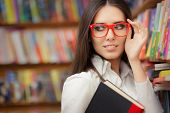picture of philosophy  - Portrait of a woman with red eyeglasses holding a book in a library - JPG