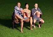 stock photo of watching movie  - three friends watching a movie at cinema outdoors - JPG