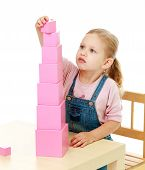 stock photo of cylinder pyramid  - Little girl collects the pink pyramid Childhood education development school concept - JPG