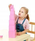 stock photo of montessori school  - Little girl collects the pink pyramid Childhood education development school concept - JPG