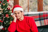 stock photo of sad christmas  - Young man sitting on the couch with santa hat in deep thoughts at home - JPG