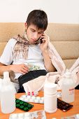picture of home remedy  - Sick Teenager with Cellphone checking the Wallet on the Sofa at the Home - JPG