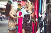 foto of thrift store  - two young women with clothes at the city mall - JPG