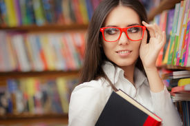 pic of nerd glasses  - Portrait of a woman with red eyeglasses holding a book in a library - JPG