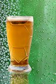 foto of ice crystal  - Froth beer glass with reflection on ice crystals and drips green background - JPG