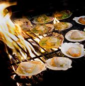 stock photo of flame-grilled  - Grilled scallops topped with butter garlic and parsley on flaming grill - JPG