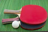 stock photo of ping pong  - Two table tennis rackets and a ping pong ball on green surface - JPG