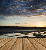 stock photo of tide  - Beautiful sunrise reflected in low tide water pools on beach landscape with wooden planks floor - JPG