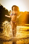 stock photo of woman bikini  - Sexy brunette woman in swimsuit running in river water - JPG