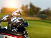 picture of driver  - Golf clubs drivers over green field background. Summer sunset ** Note: Shallow depth of field - JPG