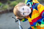 Постер, плакат: Kid Boy In Safety Helmet And Colorful Raincoat Riding Bike Outdoors